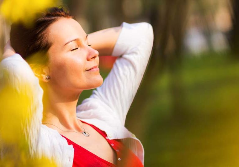Portrait of a young beautiful woman with eyes closed smiling in a sunny spring day