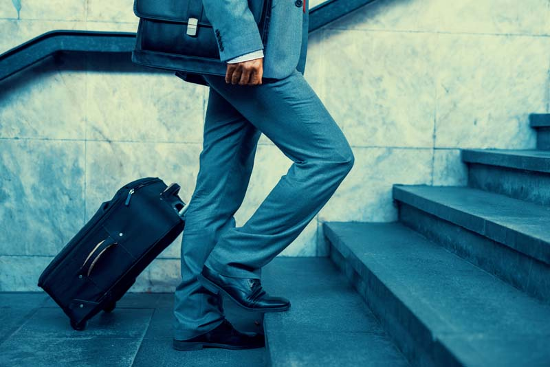 Close up of businessman carrying suitcase while walking through a passenger boarding bridge.